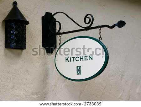 "Old rusty lantern and ""Kitchen"" sign on stucco wall - stock photo"