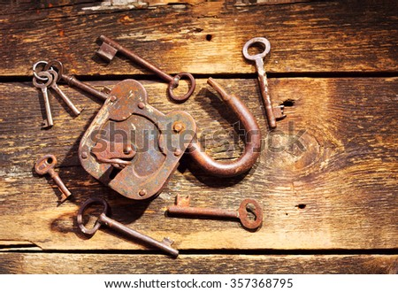 old rusty lock and keys on wooden table - stock photo