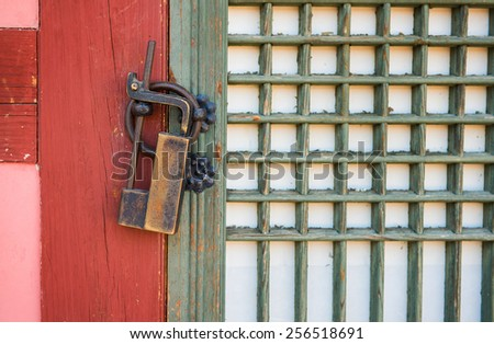 Old rusty lock on the wooden gate - stock photo
