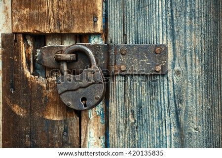 Old rusty lock on the wooden gate
