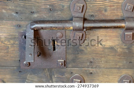 old rusty lock with big deadbolt to close the door of the castle - stock photo