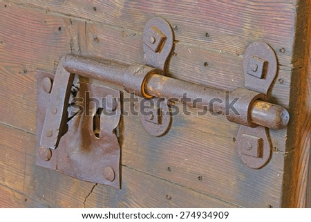 old rusty lock with big deadbolt to close the door of the medieval castle - stock photo