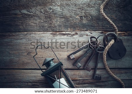 Old rusty lock with keys, vintage lamp, bottle from clay and rope on wooden board. Top view. Retro stylized photo. - stock photo