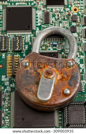 Old rusty locked padlock on computer mainboard - information or data security concept - stock photo
