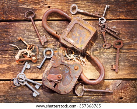 old rusty locks and keys on wooden table - stock photo