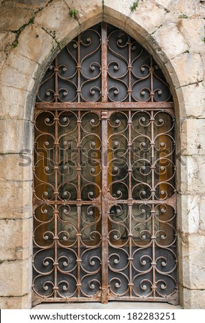 Old rusty medieval wooden door with metal motif decoration in Rocamadour, France - stock photo