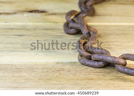 old rusty metal chain on wooden background for your text or copy space - stock photo