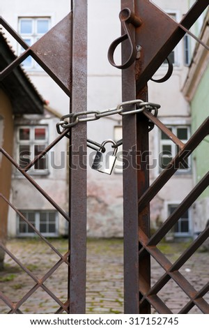 Old rusty metal gate locked with chain and padlock. - stock photo
