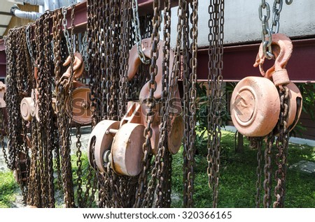 Old rusty metal hoist chain and pulley- Several old industrial chain and pulley - stock photo