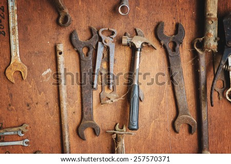 Old rusty metal key tools hanging in the workshop on the shelf.  - stock photo