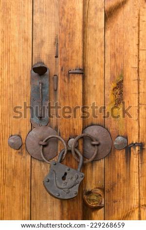 Old rusty metal lock on a wooden door - stock photo