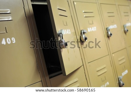 Old, rusty, metal lockers with locks. Represents concepts such as safety, security, theft, or general themes such as sports.