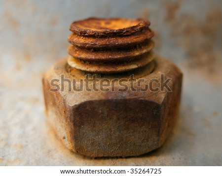 Old rusty metal nut on iron water valve pipe - stock photo
