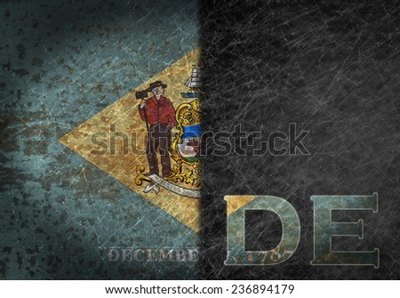 Old rusty metal sign with a flag and state abbreviation - Delaware - stock photo