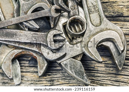Old rusty metallic spanners on wooden table - stock photo