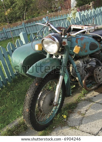 Old, rusty motorcycle at countryside standing near fence - stock photo