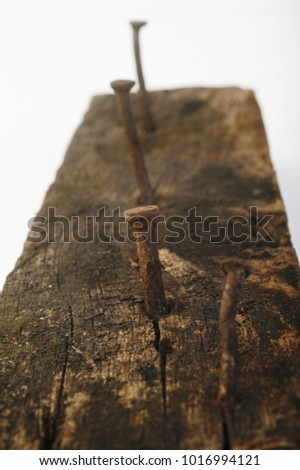 old rusty nail in wooden background