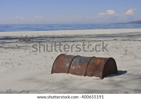 Old Rusty Oil Barrel Buried in Sand, End of Oil Age - stock photo
