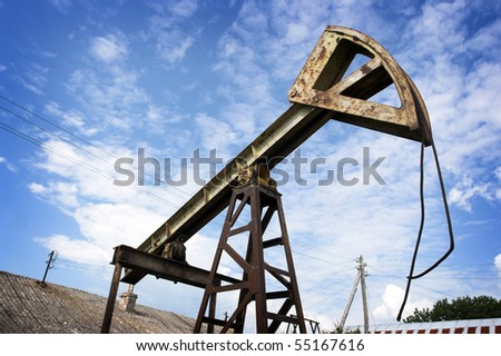 Old rusty oil pump jack against the sky - stock photo