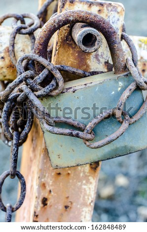 old rusty padlock holding chain - stock photo