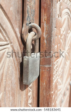 Old rusty padlock on a wooden door with carvings