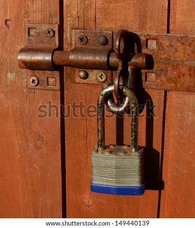 Old rusty padlock on a wooden shed door, shining in the summer sun