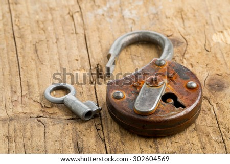 Old rusty padlock with open latch and key on wooden background - stock photo