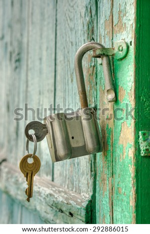 Old rusty padlock with two keys on a wooden door - stock photo