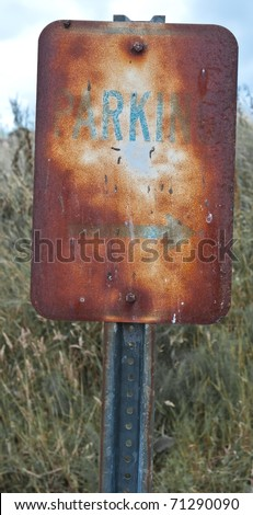Old rusty parking sign - stock photo