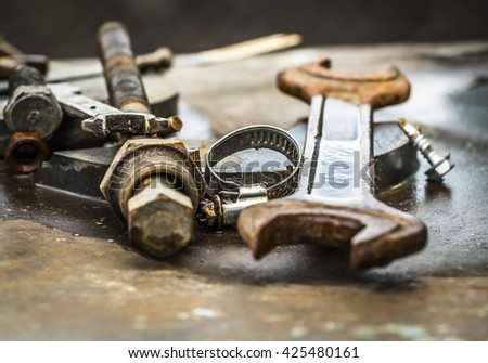 Old rusty parts and tools for repair of machinery - stock photo