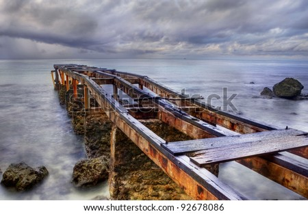 Old rusty pier located at Ciputih-Bali shot in a cloudy morning - stock photo