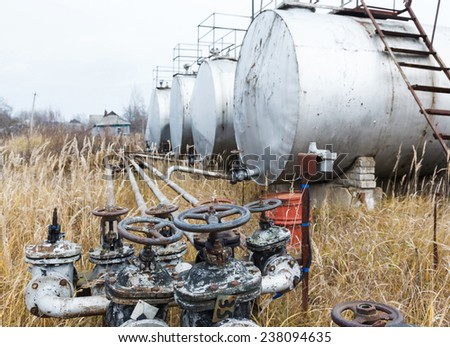 Old rusty pipes, valves and tanks at an abandoned oil refinery - stock photo