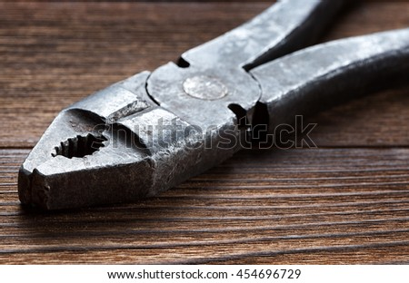 old rusty pliers on wooden background - stock photo
