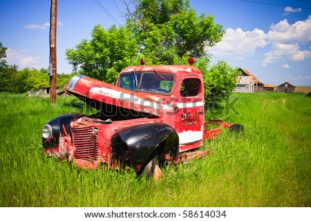 Old rusty red farm truck fading in time. - stock photo