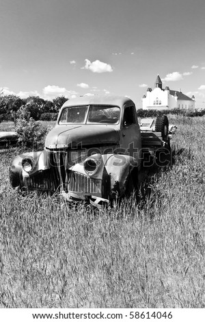 Old rusty red farm truck fading in time in the field by a church. - stock photo