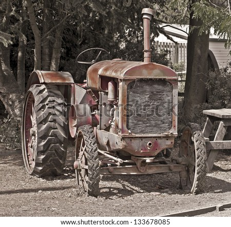 Old rusty red vintage tractor - stock photo