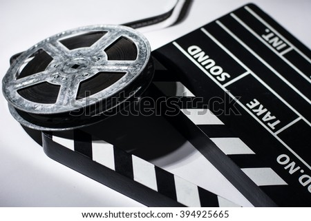 Old rusty roll of film and cinema clap. - stock photo