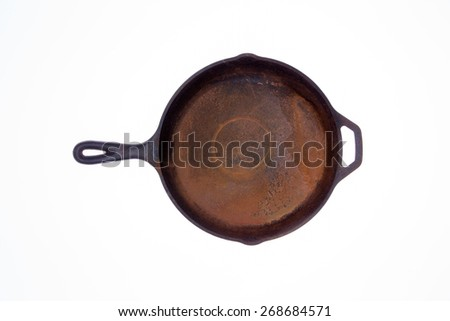 Old rusty round black cast iron frying pan viewed from above isolated on a white background centered in the frame - stock photo
