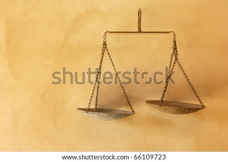 Old rusty scales hanging on a wall - stock photo