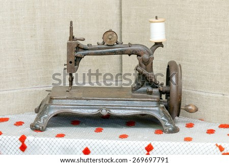Old rusty sewing machine on a white tablecloth - stock photo