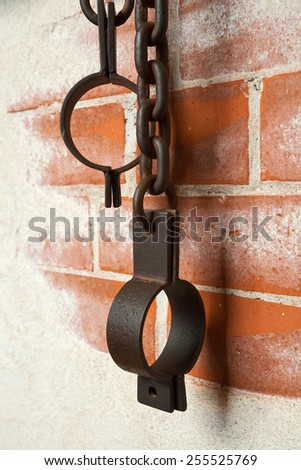 Old rusty shackles on a brick wall - stock photo