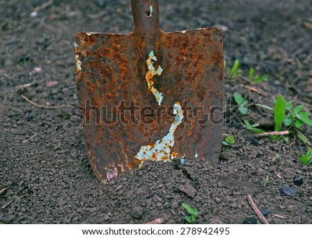 old rusty shovel stuck in the ground