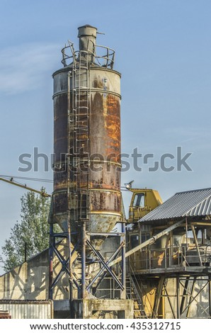 Old,rusty silos of sand at gravel pit with machinery in background