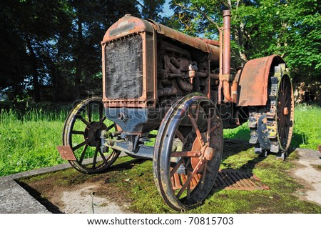 Old rusty small tractor in rural grove - stock photo