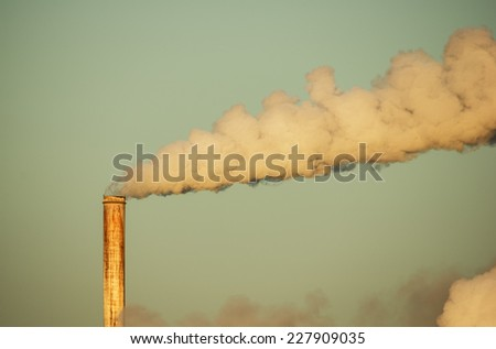 old rusty smokestack with plume of smoke lit by early morning light - stock photo