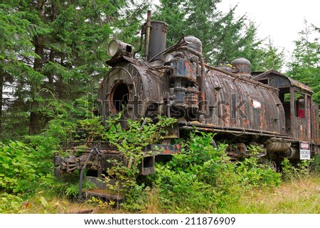 Old rusty steam locomotive in an abandoned railroad overgrown with bushes and trees. - stock photo