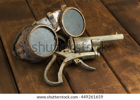 Old rusty steampunk goggles with a revolver on wooden desk - stock photo