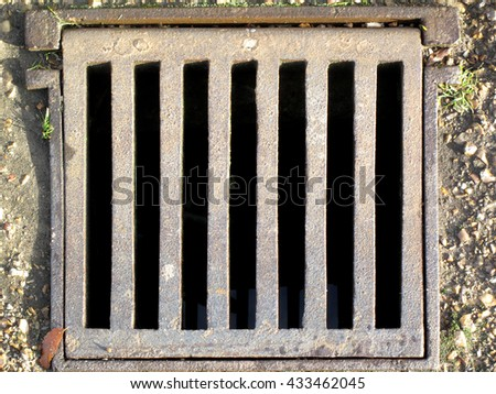 Old rusty storm and flood street drain - stock photo