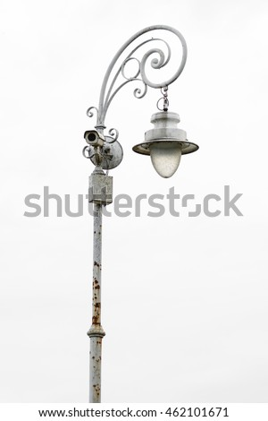 Old, rusty, street lamp post with a security camera of blue sky background. Lamp post with security camera. Pole with lights and recording device. Isolated on white background
