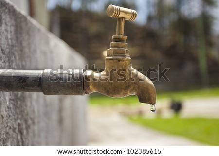 old rusty tap leaking water - stock photo